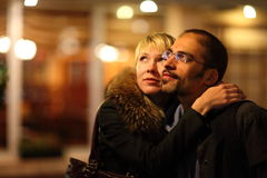 Coldly nightly street. woman is emracing her man. Focus on man's face royalty free stock photography