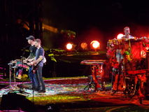 Coldplay in Concert. Three members of the band Coldplay, including Chris Martin at the piano and others on drums, performing a song in concert on a stage lit Stock Image