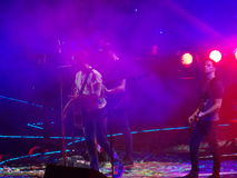 Coldplay in Concert. Three members of the band Coldplay performing a song in concert Royalty Free Stock Photography