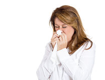 Colds and allergies. Closeup portrait of a miserable, sick adult woman with allergy, cold, blowing her nose with paper tissue, isolated on white background Stock Images