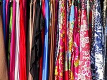 Coleção colorida da roupa firmemente embalada na cremalheira fotos de stock