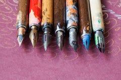Coleção da pena de fonte Acessórios caligráficos, penas coloridas envelhecidas do artista, fundo de papel cor-de-rosa textured of Foto de Stock Royalty Free