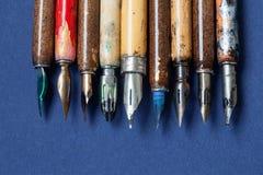 Coleção da pena de fonte Acessórios coloridos caligráficos, fundo textured do papel azul Conceito da oficina do artista Imagem de Stock