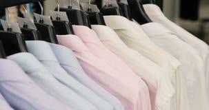Coleção da roupa bonita nova que pendura em ganchos em uma loja video estoque