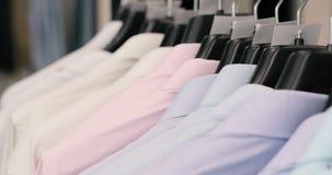 Coleção da roupa bonita nova que pendura em ganchos em uma loja filme