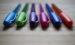 Coleção das penas coloridas colocadas em uma tabela imagem de stock royalty free