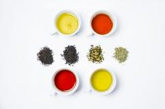 Coleção de chás diferentes em uns copos com folhas de chá em um fundo branco Fotos de Stock