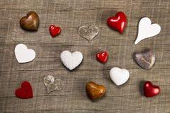 Coleção de corações vermelhos, brancos e marrons diferentes em vagabundos de madeira Foto de Stock
