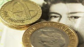A coleção de moedas de libra britânica e uma cinco-libra notam lentamente o giro video estoque