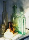 Colecci?n de botellas del vintage en luz del sol con las sombras Cierre para arriba imágenes de archivo libres de regalías