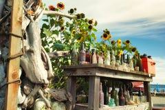 Colección de botellas viejas en una tabla de madera para la venta Foto de archivo