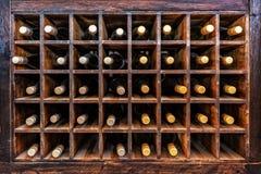 Colección de botellas de vino en los casos de madera imagen de archivo libre de regalías