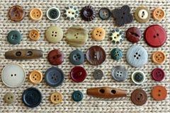 Colección de botones del vintage dispersados en fondo de la tela Imagenes de archivo