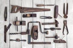 Colección de herramientas antiguas de la carpintería en la tabla de madera Fotos de archivo libres de regalías
