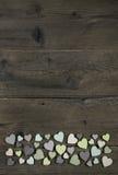 Colección de muchos corazones hechos a mano en colores naturales en la madera vieja Foto de archivo