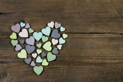 Colección de muchos corazones hechos a mano en colores naturales en la madera vieja Imagen de archivo