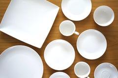 Colección de placas de la porcelana en la tabla de madera Fotos de archivo