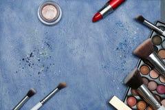 Colección de productos de maquillaje en fondo azul con el copyspace Fotos de archivo libres de regalías