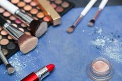 Colección de productos de maquillaje en fondo azul con el copyspace Fotografía de archivo libre de regalías