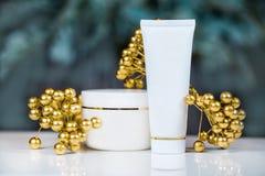 Colección de tres tubos para la crema o la loción con la decoración del oro, gotas, en el fondo blanco Foto de archivo