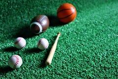 Colección de varias bolas de juego del deporte tales como fútbol, fútbol, y tenis, volando en un fondo verde imagenes de archivo
