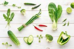 Colección de verduras orgánicas verdes con acento rojo del chile en la tabla de madera Fotografía de archivo