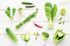 Colección de verduras orgánicas verdes con acento rojo del chile en la tabla de madera Foto de archivo
