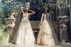 eb5358c0f00 Colección de vestidos de boda elegantes en el escaparate de la tienda Dos  maniquíes que llevan