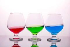 Colección de vidrios con las bebidas coloreadas fotos de archivo libres de regalías
