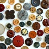 Colección del botón del vintage dispersada en el fondo blanco Fotos de archivo libres de regalías