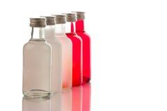 Colección encendida parte posterior de botellas de cristal coloridas Fotos de archivo