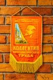 Colectividad soviética del banderín del trabajo del comunista contra un ladrillo w fotografía de archivo libre de regalías