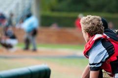 Colector del béisbol que se inclina sobre la cerca del cobertizo que mira la cámara Fotos de archivo libres de regalías