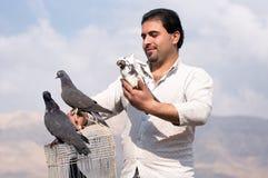 Colector iraquí de la paloma que sostiene amablemente una paloma Imagen de archivo libre de regalías
