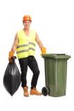 Colector joven del despilfarrador que vacia un bote de basura Foto de archivo