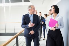 Colega de Communicating With Female del hombre de negocios mientras que camina encendido imagen de archivo libre de regalías
