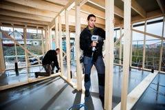 Colega de Drilling Plank While del carpintero que trabaja en la construcción fotos de archivo libres de regalías