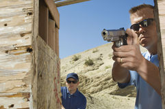 Colega de observação do homem que aponta a arma da mão Imagens de Stock Royalty Free