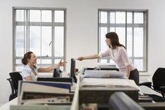 Colega de Passing Document To de la empresaria sobre el escritorio en oficina Imagenes de archivo