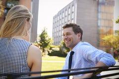Colega de Talking To Female do homem de negócios na ruptura no parque foto de stock royalty free