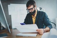 Colega de trabalho novo que trabalha no escritório lightful no computador ao sentar-se na tabela de madeira O homem analisa o ori Fotografia de Stock Royalty Free