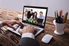 Colega de Video Conferencing With del empresario en el ordenador portátil fotos de archivo