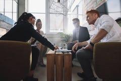 Colega do negócio que senta-se na tabela durante a reunião incorporada foto de stock