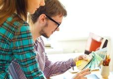 Colega joven - mujer del manand que mira a una paleta de la pintura del color Foto de archivo libre de regalías