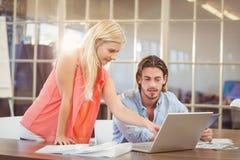 Colega masculino de explicación de la empresaria en el ordenador portátil Imagen de archivo