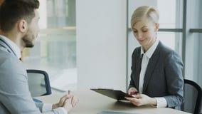 Colega masculino que da el contrato para firmar a la empresaria rubia en traje y discutir los detalles en oficina moderna