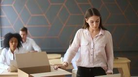 Colega que apoya confortando la caja de embalaje despedida encendida de la mujer en el lugar de trabajo almacen de metraje de vídeo