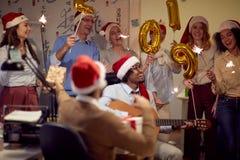 Colegas acertados en los casquillos de Papá Noel que se divierten la Navidad imagenes de archivo