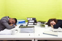 Colegas adormecidos em sua mesa respectiva Imagens de Stock Royalty Free