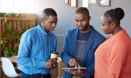 Colegas africanos del trabajo que discuten el papeleo digital junto en una oficina Imagen de archivo libre de regalías